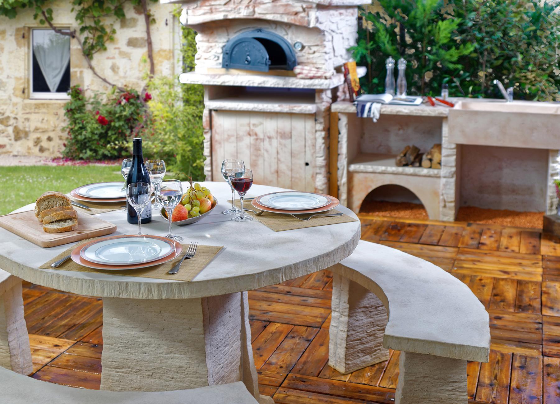 Cuisine d\'été extérieure avec four à pizza et salon de jardin
